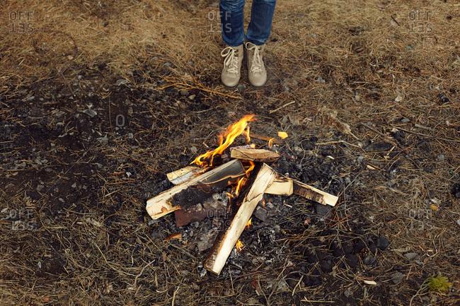Caucasian teenage girl standing at campfire