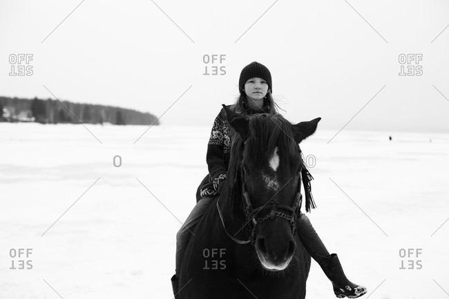 Caucasian teenage girl riding horse in snowy field