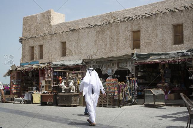 Man walking outside market on Doha sidewalk, Doha, Qatar