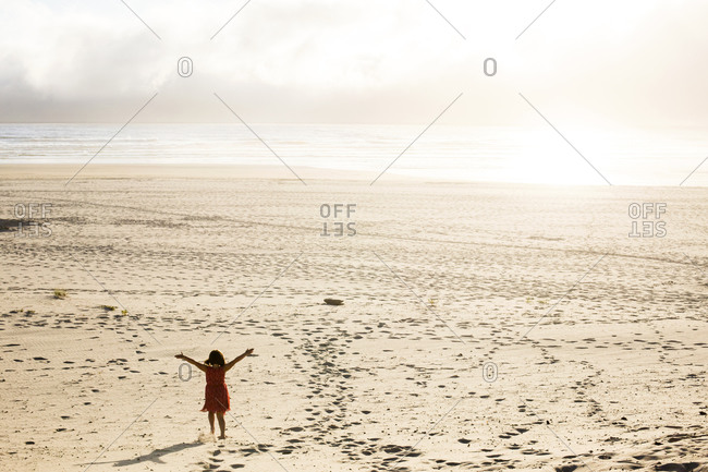 Caucasian girl standing with arms outstretched on beach