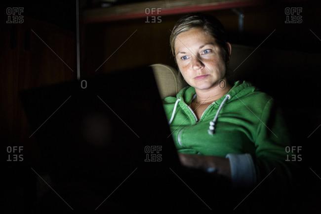 Caucasian woman using laptop at night