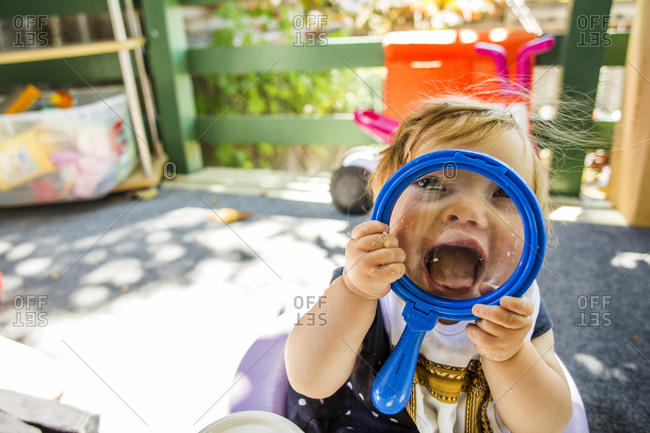 Caucasian baby girl playing on patio