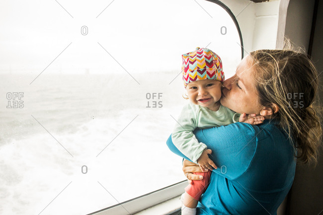 Caucasian mother kissing baby daughter at window