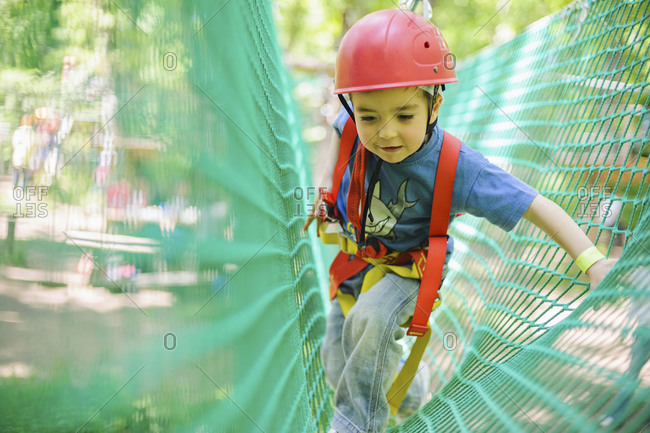 Caucasian boy in harness climbing on net