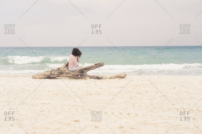 Woman sunbathing on driftwood log on beach