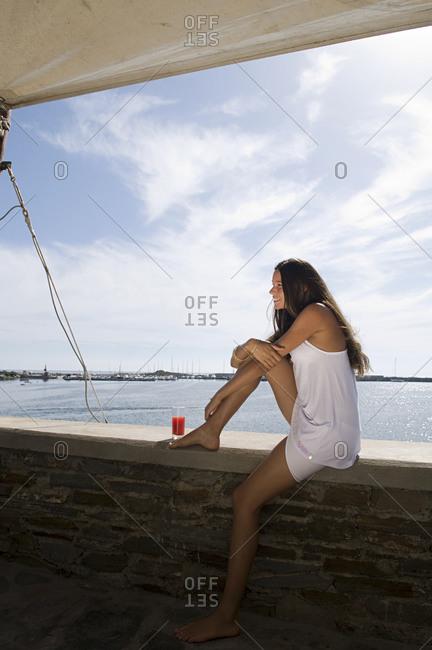 Woman sitting on wall overlooking ocean