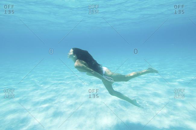 Underwater view of woman swimming in ocean