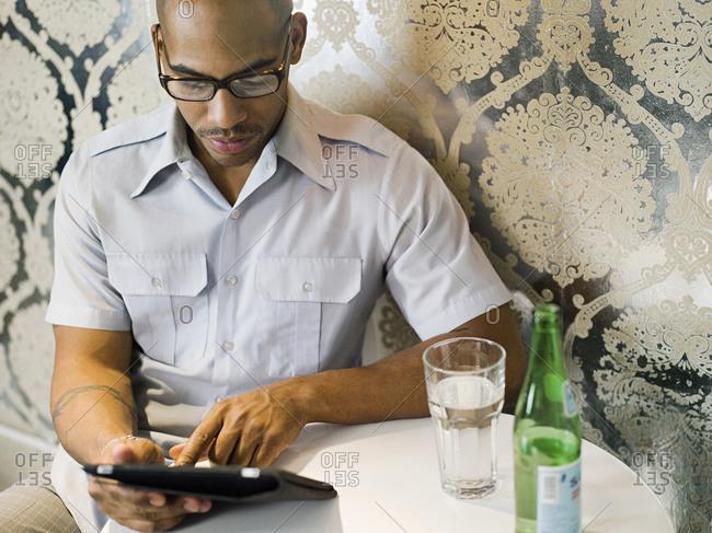 African American man using digital tablet in restaurant