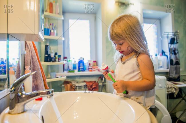 Caucasian girl brushing her teeth in bathroom