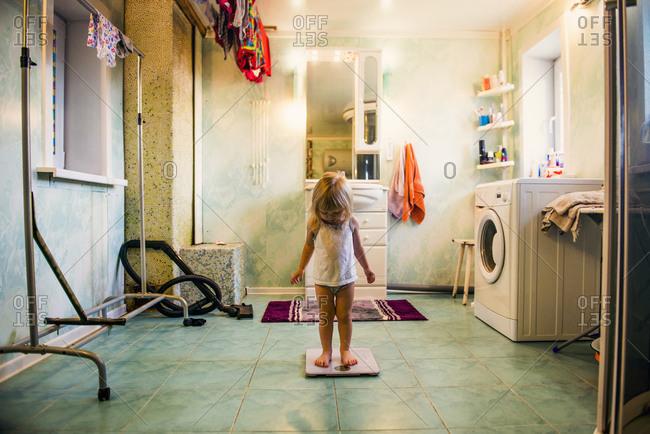 Caucasian girl standing on scale in bathroom