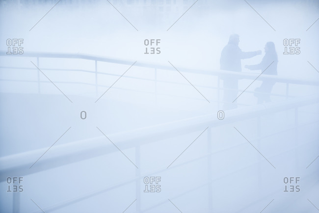 People standing on walkway in mist