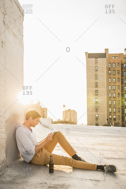 Caucasian man using cell phone on urban rooftop