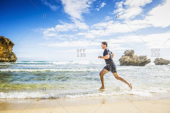 Caucasian man jogging on beach