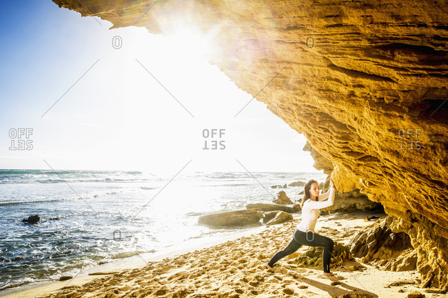 Caucasian woman practicing yoga under rock formation on beach