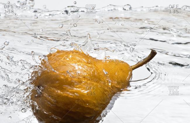Close up of pear splashing in water