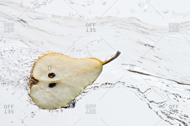 Close up of halved pear splashing in water