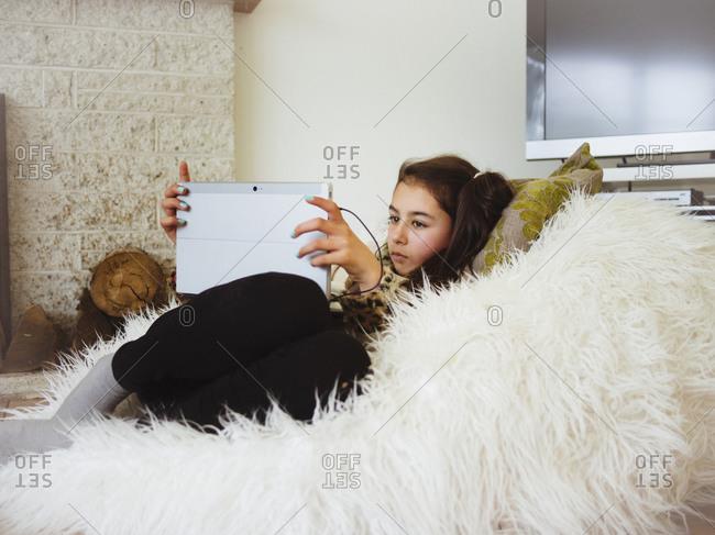Mixed race girl using digital tablet in bean bag