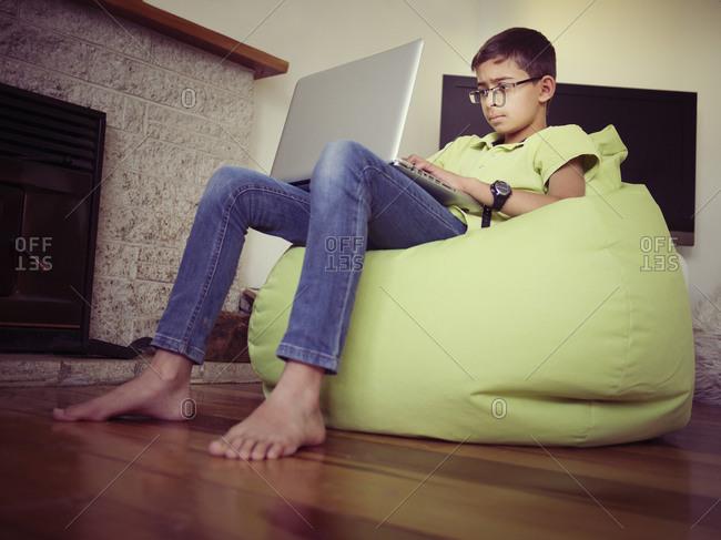 Mixed race boy using laptop in bean bag