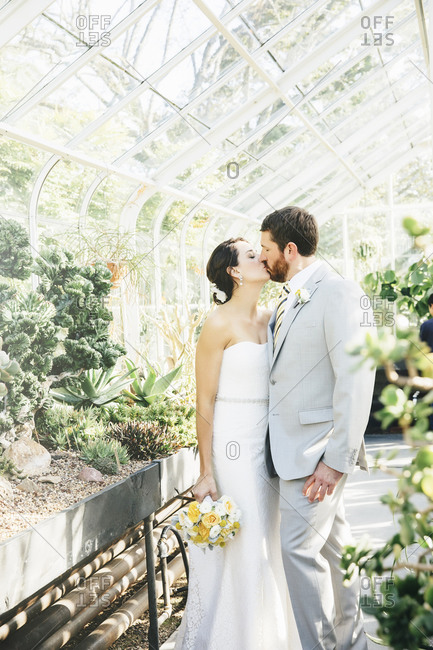 Caucasian bride and groom kissing in greenhouse