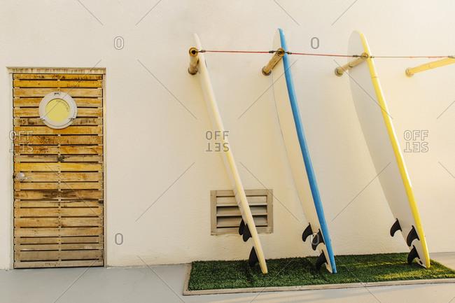 Surfboards in rack on building exterior