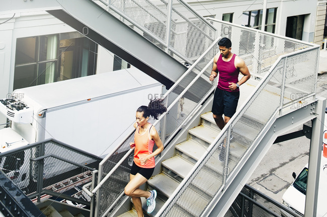 Couple jogging on city steps