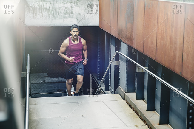 Indian man jogging on city steps