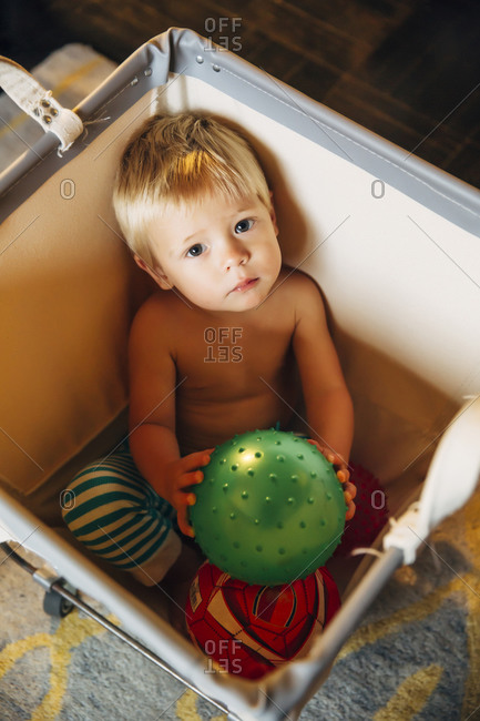 Mixed race boy playing in laundry hamper