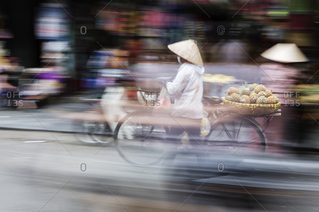 Blurred view of traffic and merchants on city street