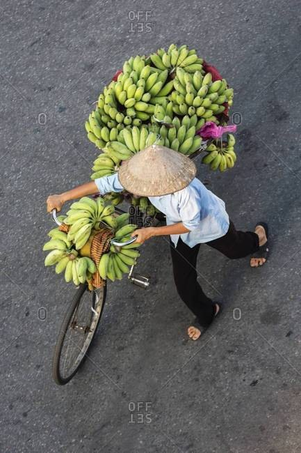 High angle view of vendor pushing bicycle with bananas