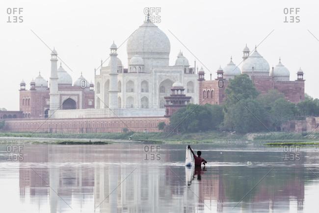 Fisherman pulling net from river by Taj Majal, Agra, Uttar Pradesh, India