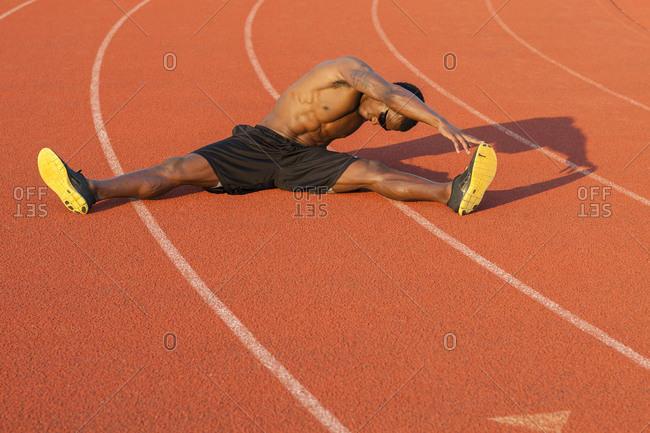 Black athlete stretching on track in sports field