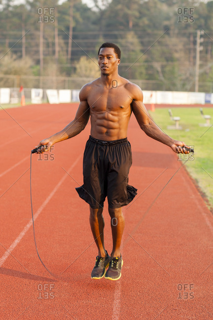 Black athlete jumping rope on track in sports field