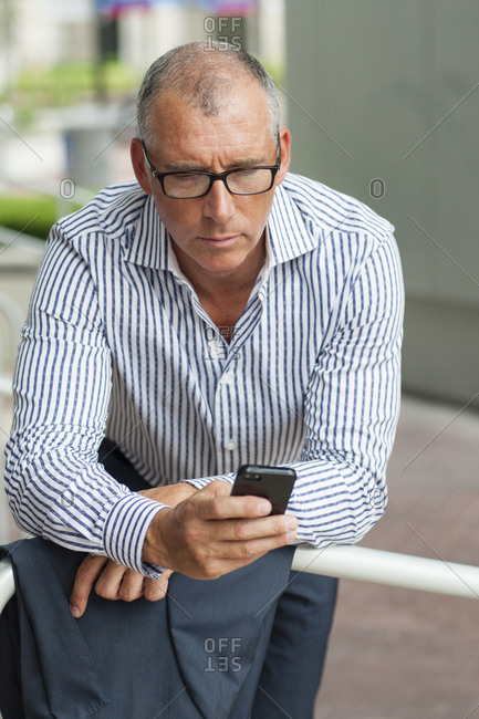 Caucasian businessman using cell phone at banister