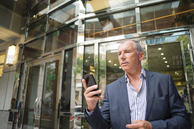 Caucasian businessman using cell phone outside office