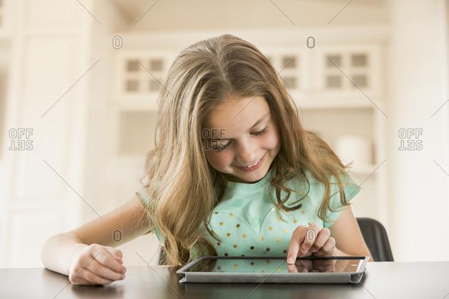 Caucasian girl using digital tablet at table