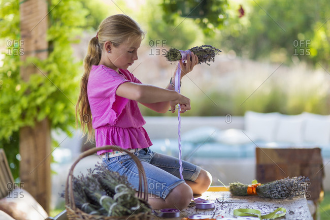 Caucasian girl wrapping dried flower bundle