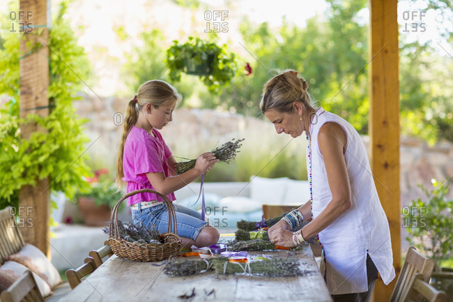 Caucasian mother and daughter making dried flower bundles