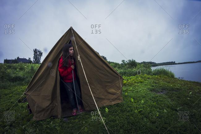 Caucasian girl standing in tent at campsite