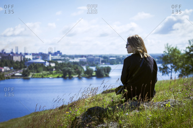 Caucasian woman admiring cityscape from rural hilltop