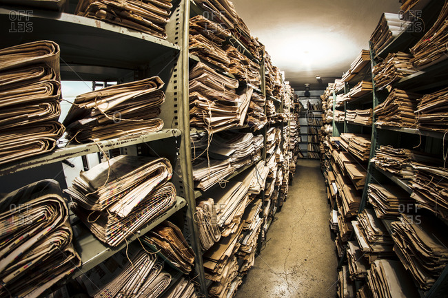 Stacks of old newspapers in library archive