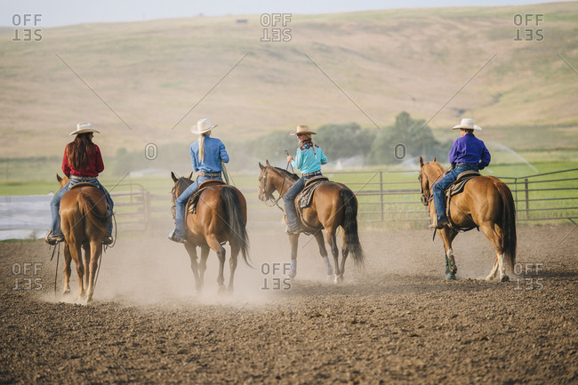 Cowgirls and cowboy riding horses on ranch