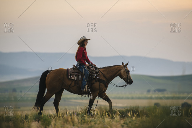Caucasian cowgirl riding horse in rural field