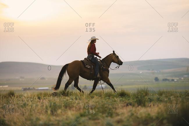 Caucasian cowgirl riding horse in rural field