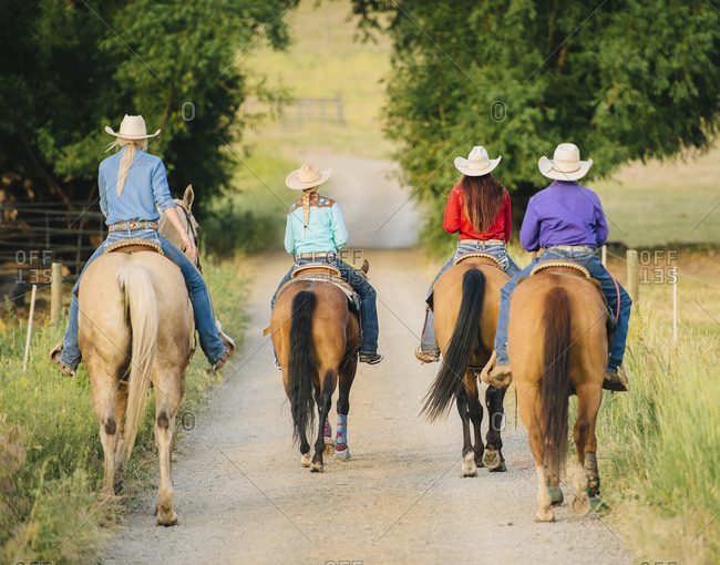 Cowgirls and cowboy riding horses in rural road