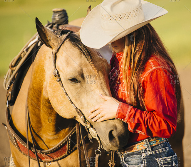 Caucasian cowgirl petting horse on ranch