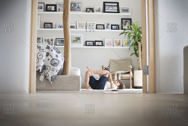 Hispanic boy playing on living room floor