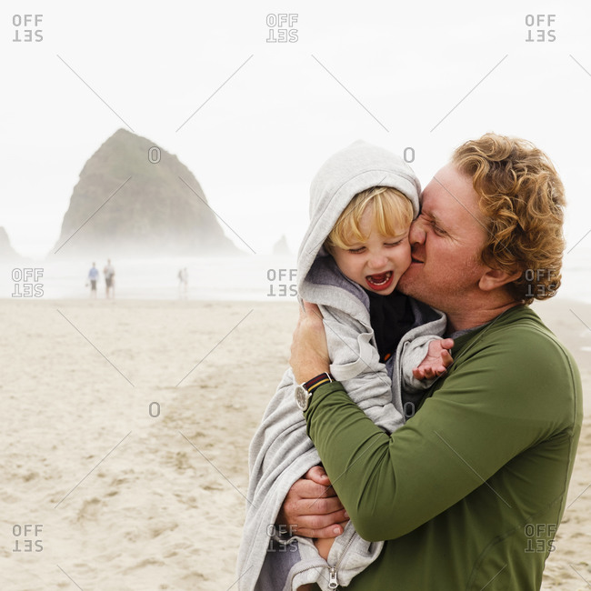 Caucasian father kissing son on beach