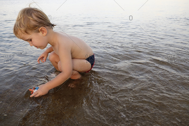 Caucasian boy playing in water on beach