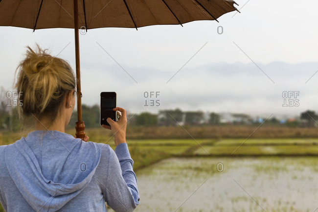 Caucasian woman photographing rural rice fields