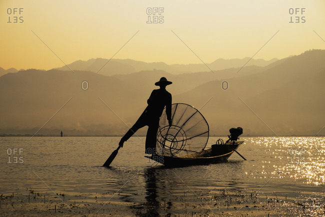 Asian fisherman rowing canoe on rural lake